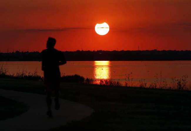 A jogger runs in front of the sun near the end of a partial solar eclipse at Lake Hefner in Oklahoma City, Thursday, Oct. 23, 2014. | AP Photo