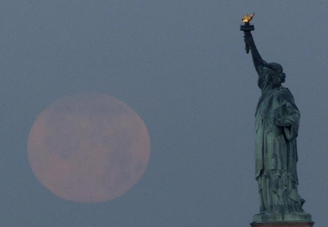 A supermoon sits in the sky larger than life behind the State of Liberty. | AP Photo