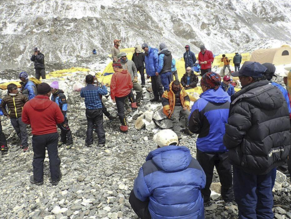 In this photo provided by Azim Afif, people are examined for injuries and prepared for helicopter evacuation at the International Mount Guide (IMG) camp at Everest Base Camp, Nepal on Sunday, April 26, 2015. An avalanche triggered by Nepal's...
