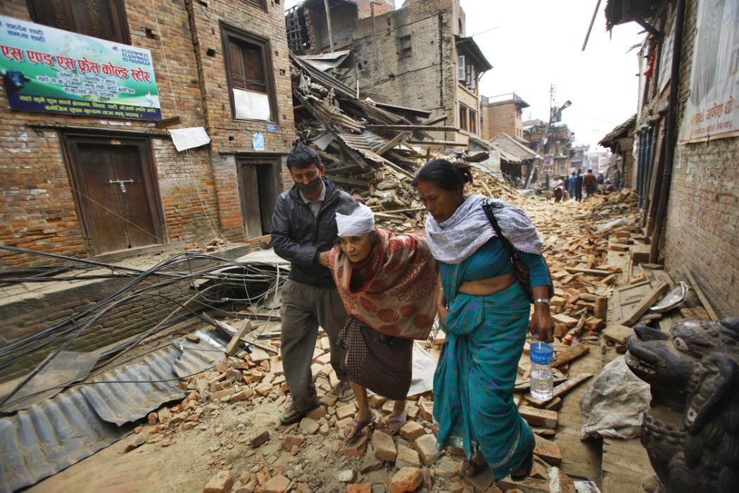 An elderly injured woman is taken to her home after treatment in Bhaktapur near Kathmandu, Nepal, Sunday, April 26, 2015. A strong magnitude 7.8 earthquake shook Nepal's capital and the densely populated Kathmandu Valley before noon Saturday,...