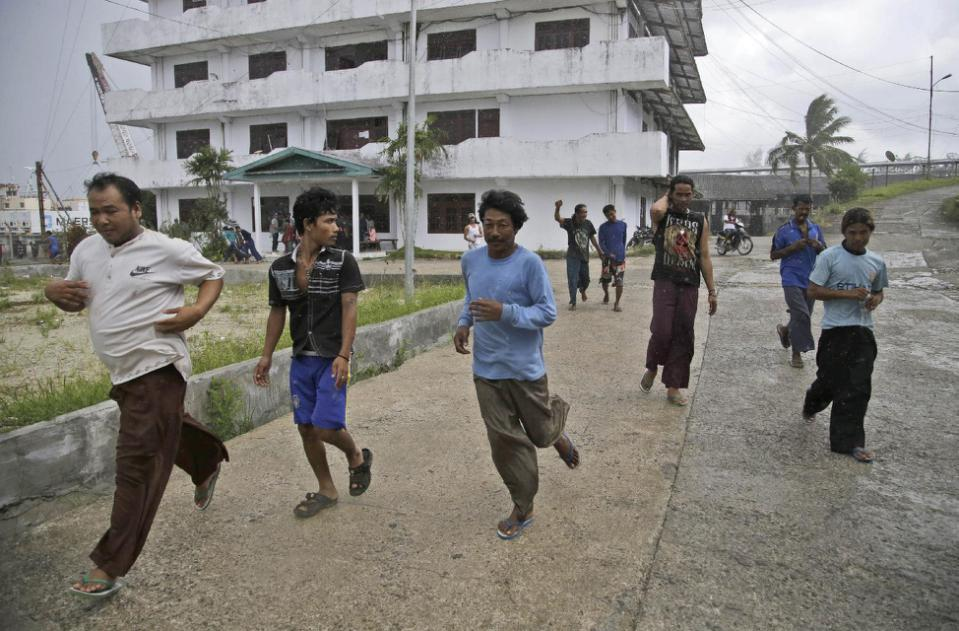 Burmese fishermen run to collect their belongings after being informed that they can leave, at the compound of Pusaka Benjina Resources fishing company in Benjina, Aru Islands, Indonesia, Friday, April 3, 2015. Hundreds of foreign fishermen on...