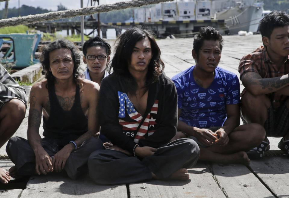 Foreign fishermen sit on the ground before being questioned by Indonesian officials at the compound of Pusaka Benjina Resources fishing company in Benjina, Aru Islands, Indonesia, Friday, April 3, 2015. Officials from three countries are traveling...