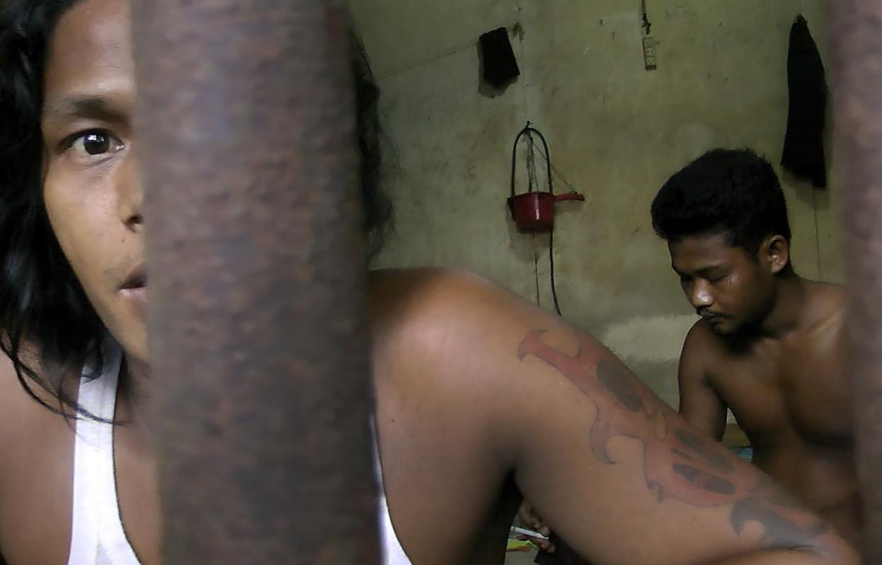 In this Thursday, Nov. 27, 2014 image from video, Kyaw Naing, a slave from Myanmar, looks through the bars of a cell at the compound of a fishing company in Benjina, Indonesia. An estimated 4,000 foreign fishermen are stranded on a number of...