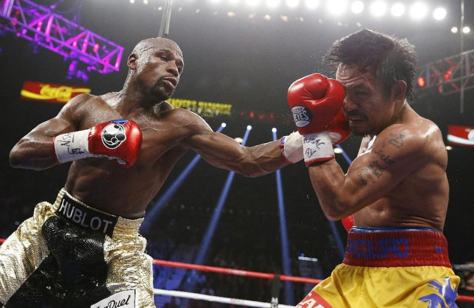Floyd Mayweather Jr., left, lands a left to the head of Manny Pacquiao, from the Philippines, during their welterweight title fight on Saturday, May 2, 2015 in Las Vegas. (AP Photo/John Locher)