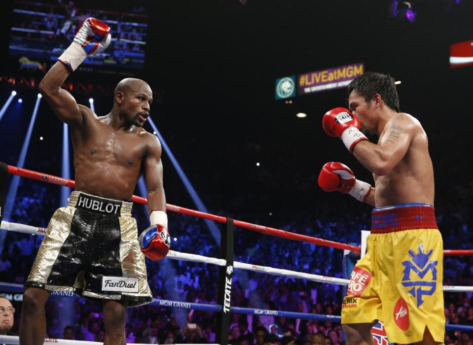 Floyd Mayweather Jr., left, celebrates during his welterweight title fight against Manny Pacquiao, from the Philippines, on Saturday, May 2, 2015 in Las Vegas. (AP Photo/John Locher)