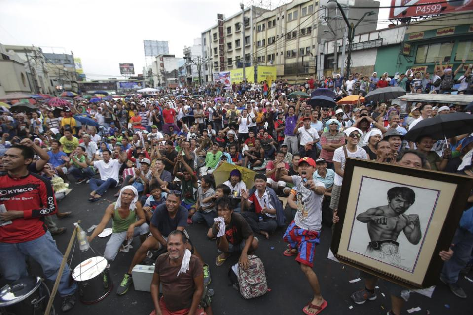 Filipinos watch a live satellite feed of the welterweight title fight between Filipino boxing hero Manny Pacquiao and Floyd Mayweather Jr. during a free public viewing in downtown Manila, Philippines on Sunday, May 3, 2015. Mayweather Jr. won the...