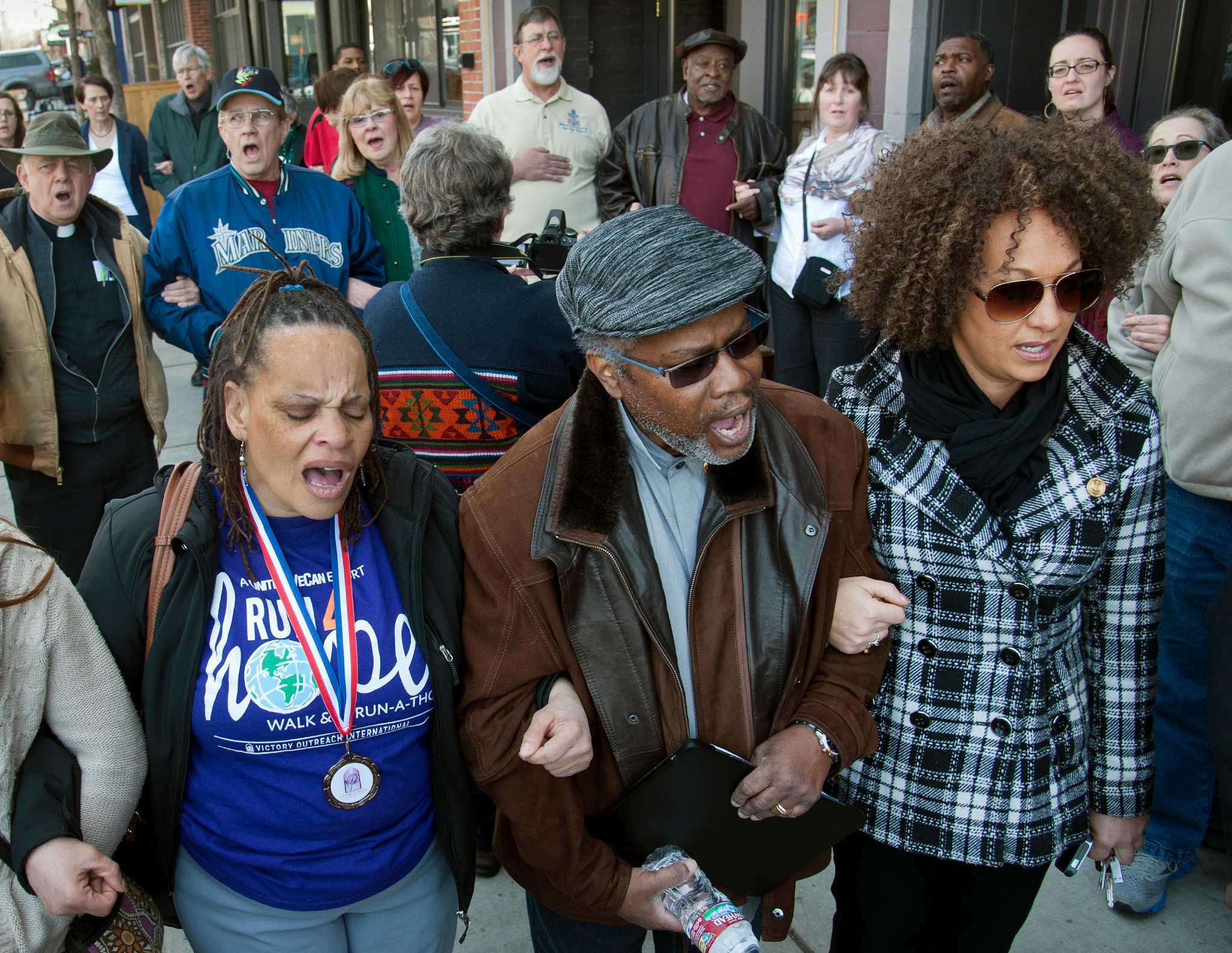 """FILE- In this Friday, March 6, 2015 file photo, from left, Della Montgomery-Riggins, Charles Thornton and Rachel Dolezal link arms and sing """"We Shall Overcome"""" at a rally in downtown Spokane, Wash. responding to a racist and threatening package..."""