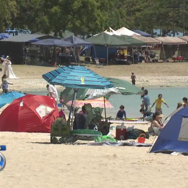 Families camp out at Ala Moana Beach Park, ready for holiday fireworks