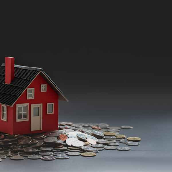 red toy house placed on table with pile of coins